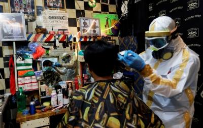 Foto: Tukang Pangkas Rambut Pakai Kostum APD
