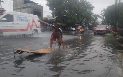 Kritik Pemko Medan, 3 Pemuda Memancing dan Berselancar saat Banjir